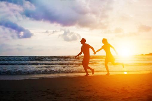 手をつないで夕日の海のビーチで走っている幸せなカップル熱帯の楽園の ...