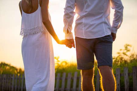 夕日を見てノスタルジックでロマンチックなカップルを後ろから見る の ...
