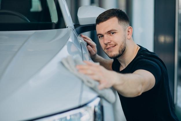 若い男が布で彼の車を研磨 | 無料の写真