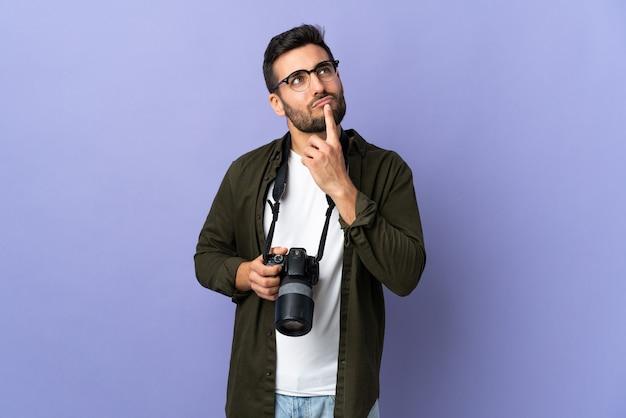 見上げている間疑いを持っている孤立した紫色の上の写真家の男 ...