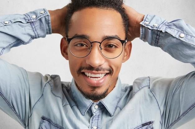 大きな丸い眼鏡の幸せな流行に敏感な男はリラックスした感じ | 無料の写真