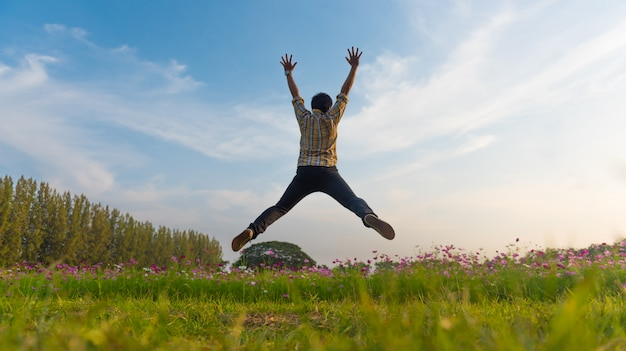 青い空に花の庭で高くジャンプ男。 | プレミアム写真
